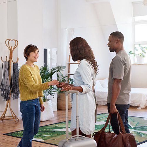Woman welcoming a couple into an Airbnb.